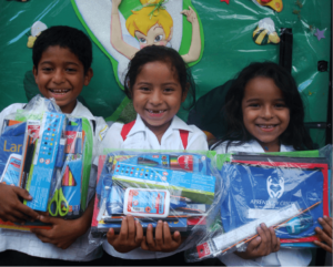three school kids holding up school supply packages