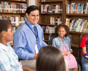 adult instructing students in a library