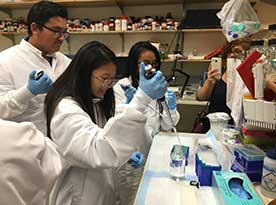 three students walking in a science lab