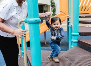 little boy on playground with woman