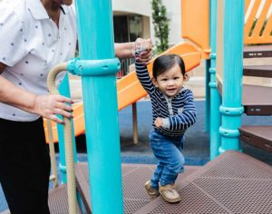 small boy with adult playing on the playground