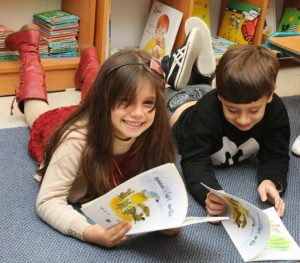 boy and girl laying on the floor with books