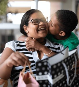 boy hugging mom and kissing her on the cheek