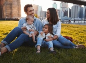 family sitting on the grass in the city