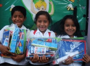two girls and a boy holding school supplies packages
