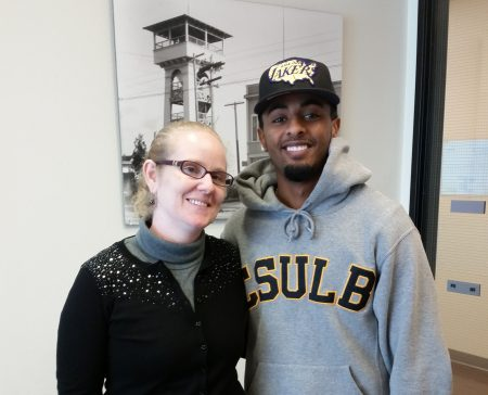 Teacher in black sweater with student in college hoodie