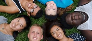 group of fellows laying on the grass in a circle