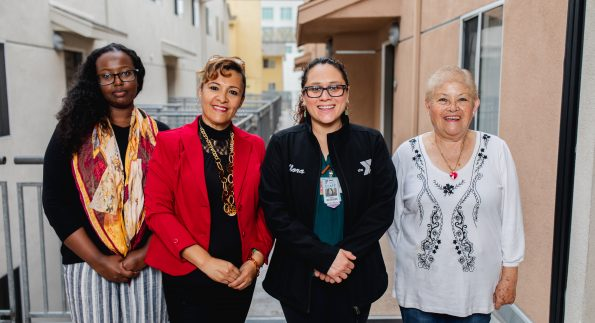 4 women smiling outside a building
