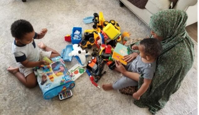A Family Childcare provider reads and plays with children she cares for in her home.